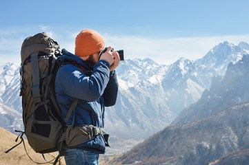 Portrait of a bearded male photographer in sunglasses and a warm jacket with a backpack on his back and a reflex camera in his hands takes pictures against the background of snow-capped mountains