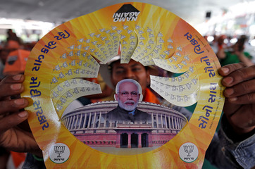 A supporter of India's PM Modi displays a paper cap with images of Modi and Indian Parliament during an election campaign rally in Junagadh