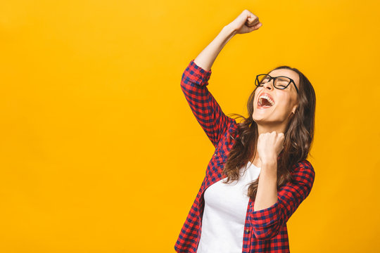 Winning success woman happy ecstatic celebrating being a winner. Dynamic energetic image of multiracial Caucasian Asian female model isolated on yellow background waist up.