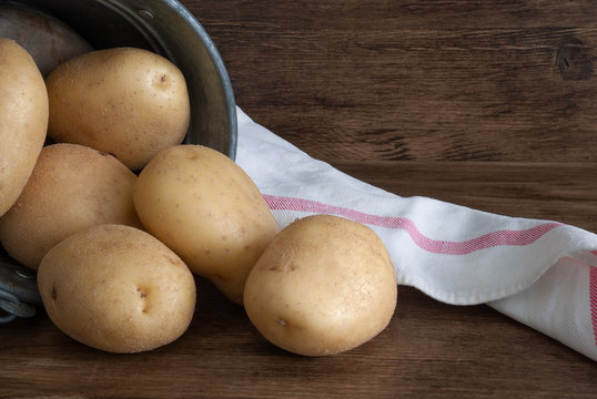 Close-up of potatoes in metal bucket with white kitchen cloth. On dark wood background