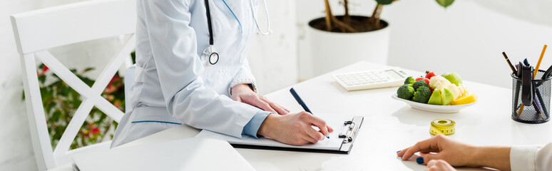 panoramic shot of nutritionist writing diagnosis near patient