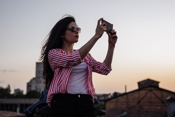 Beautiful woman standing outdoors on a sunset and taking a photo with her cell phone.
