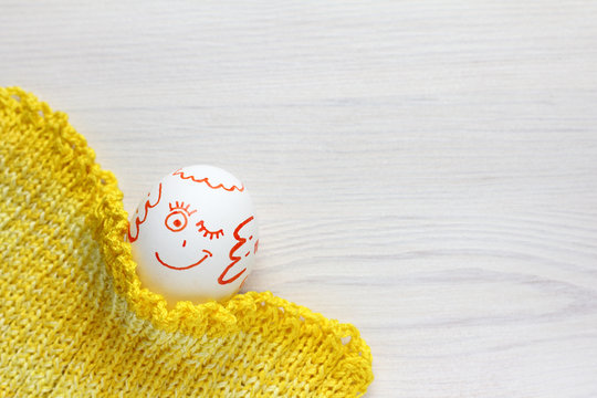 a chicken egg under a yellow blanket with a smile winks. warming emotions