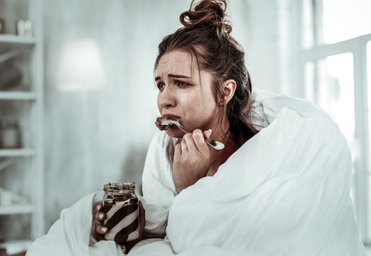 Woman eating chocolate pasta because of being stressed
