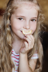 Portrait of a charming little girl with a slice of lemon