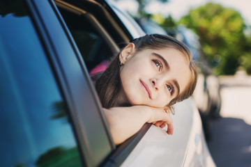 Cute child looks out the window of the car in the summer