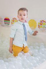 Cute boy in the children's playroom plays in the white balls on the holiday