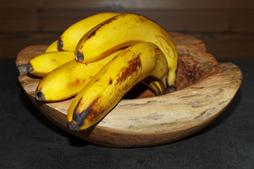 Close-up of ripe yellow bananas in a wooden bowl