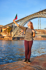 Fotobehang Nice Young woman tourist with portuguese flag enjoying beautiful landscape view on the old town with river and famous iron bridge Dom Luiz during the sunset in Porto city, Portugal