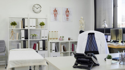 Doctor office table and chair with white lab coat on it and white paper nobody. telephone and tools on work desk by the therapy bed in clinic. bright and modern empty workplace in hospital. Wall mural