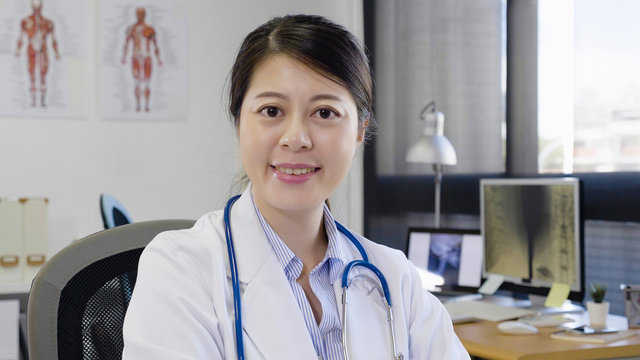 Portrait of young doctor woman with stethoscope sitting at desk in workplace hospital. asian female nurse in white lab coat face camera smiling friendly. beautiful lady in bright clinic office.