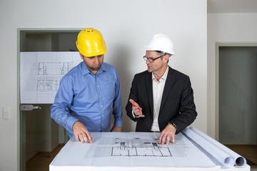 Der Architekt erklärt dem Bauherren Details des Bauplans und zeigt ihm die Planbereiche