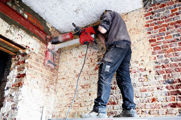Laborer pierce a big round hole in a brick wall