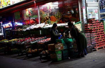 A worker serves a customer at a fruit and vegetable shop on a high street in Dagenham, east London