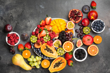 Wall Mural - Delicious fruit platter mango pomegranate raspberries papaya oranges passion fruits berries on oval serving plate on dark concrete background, selective focus, top view, copy space