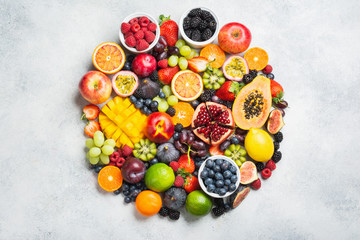 Wall Mural - Circle made of healthy raw rainbow fruits, mango papaya strawberries oranges passion fruits berries on oval serving plate on light concrete background, top view, copy space, selective focus