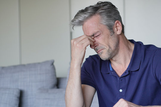 Mature man with bad headache at home