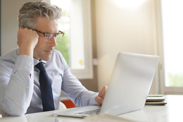 Businessman wearing glasses working in contemporary office