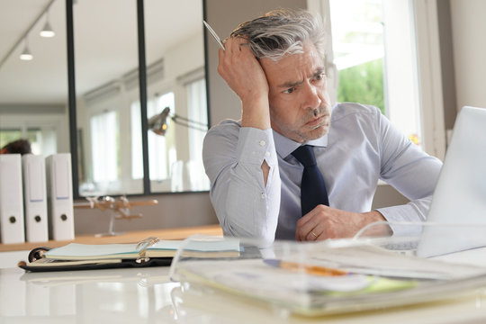 Stressed businessman working in contemporary office