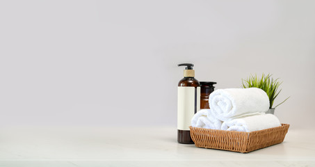 Towels in basket and spa accessory on Mable table