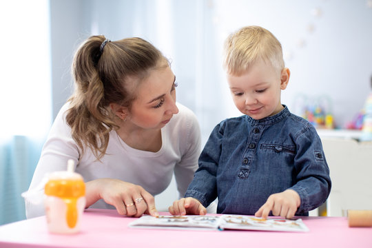 Mother or babysitter reading a book to kid. Indoors