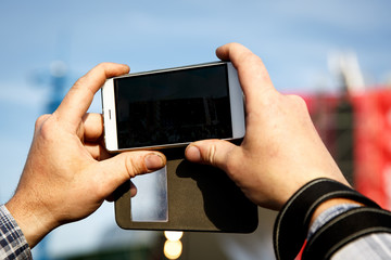 Smartphone in hand. Photographing at the summer music festival.