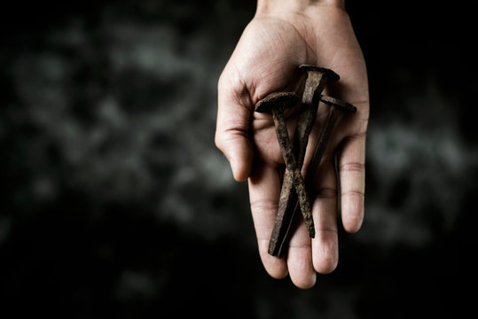 rusty nails on the hand of a man