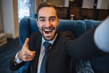 Handsome young excited businessman wearing suit