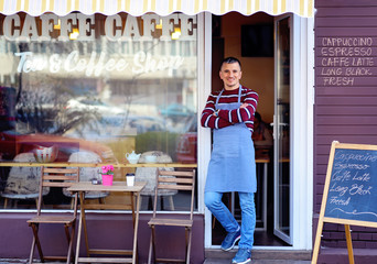 Portrait of a confident young man standing in the doorway of a coffee shop. Tea and Coffee Shop written on the window. Traffic reflection. His welcoming smile makes a great first impression