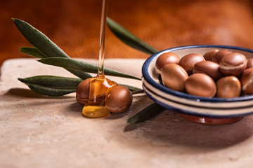 argan oil pouring over argan seeds