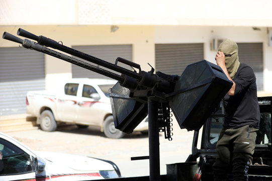 A member of Libyan internationally recognised pro-government forces stands in a military vehicle with a machine gun, on the outskirts of Tripoli