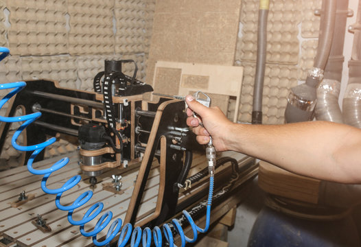 Man is removing dust from the computer numerical control machine for wooden tools. CNC equipment for maintenance control and details.