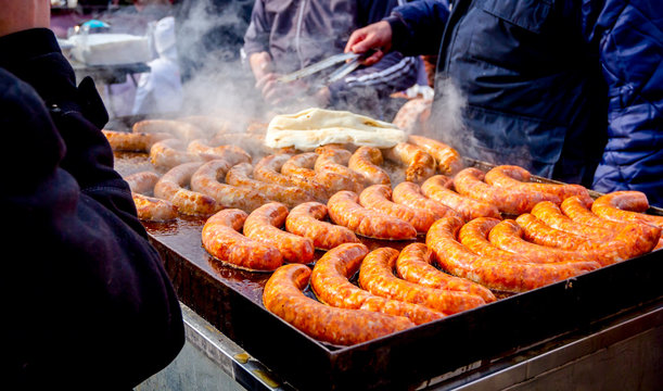 Turning delicious juicy sausages on barbecue plate with handle