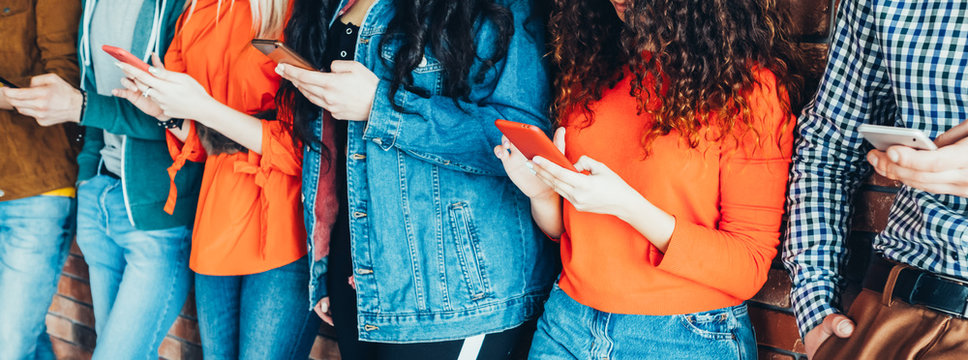 Millennials style. Young people in trendy denim outfits standing with smartphones, reading messages, posts in social networks.