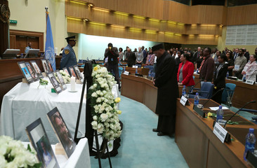 A priest pays homage next to pictures of the United Nations staff who lost their lives in the Ethiopian Airlines Flight ET 302 plane crash at the United Nations Economic Commission for Africa (UNECA) headquarters in Addis Ababa