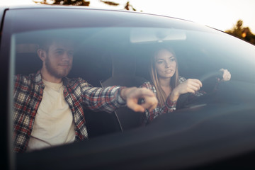 Fototapete - Male instructor and woman student, driving lesson