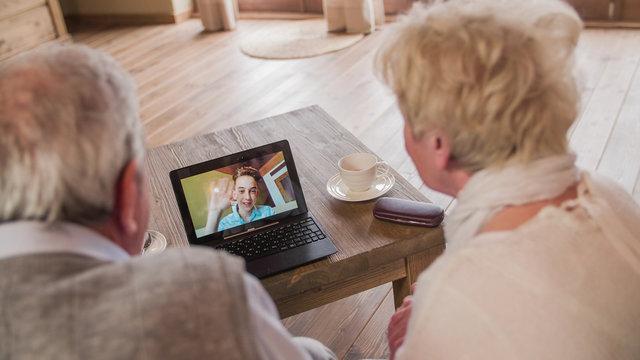 Grandchild over video call wave to grandparents