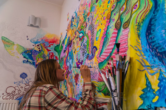 Young female artist doodling on the wall, bright psychedelic mind flow deep relaxation painting
