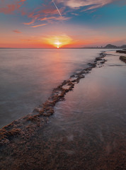 View of a sunset in a mediterranean cove with the last rays of the sun in the seascape