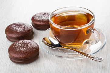 Chocolate cookies, cup of tea, spoon on saucer on table