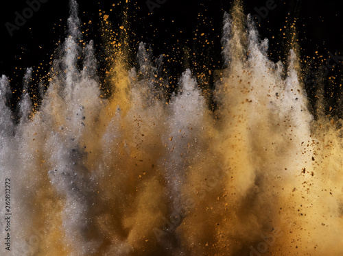 Fototapete Explosion of colored powder isolated on black
