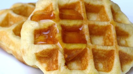 Fototapete - Pour natural honey to a pile of waffles on white background