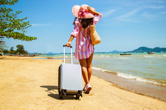 Beautiful young woman with a hat standing with suitcase on the wonderful sea background, concept of time to travel.
