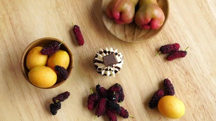 Fototapete - Top view of delicious cupcake and different kinds of fruit on a wooden board