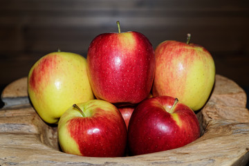 Close-up of ripe red yellow apples in a wooden bowl