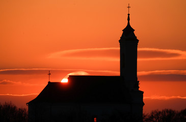 Catholic church is silhouetted during a sunset in the town of Zaslavl