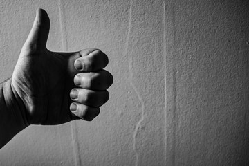 Black and white image of a hand giving a thumbs up