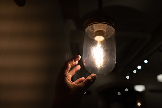Hand reaching for a vintage light bulb.