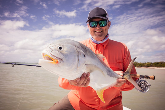 Man holding fish caught in salt water fly fishing, caribbean
