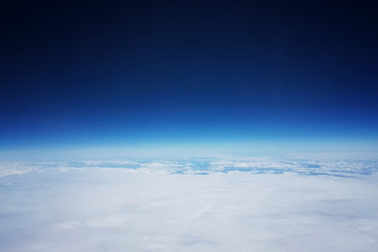 Low earth orbit - View of white clouds and mountains during the flight to the low orbit of the Earth, at the top of the blue sky and space